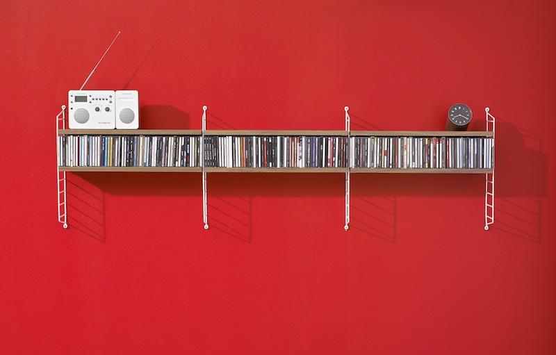 Bibliothèque string pocket sur un mur rouge