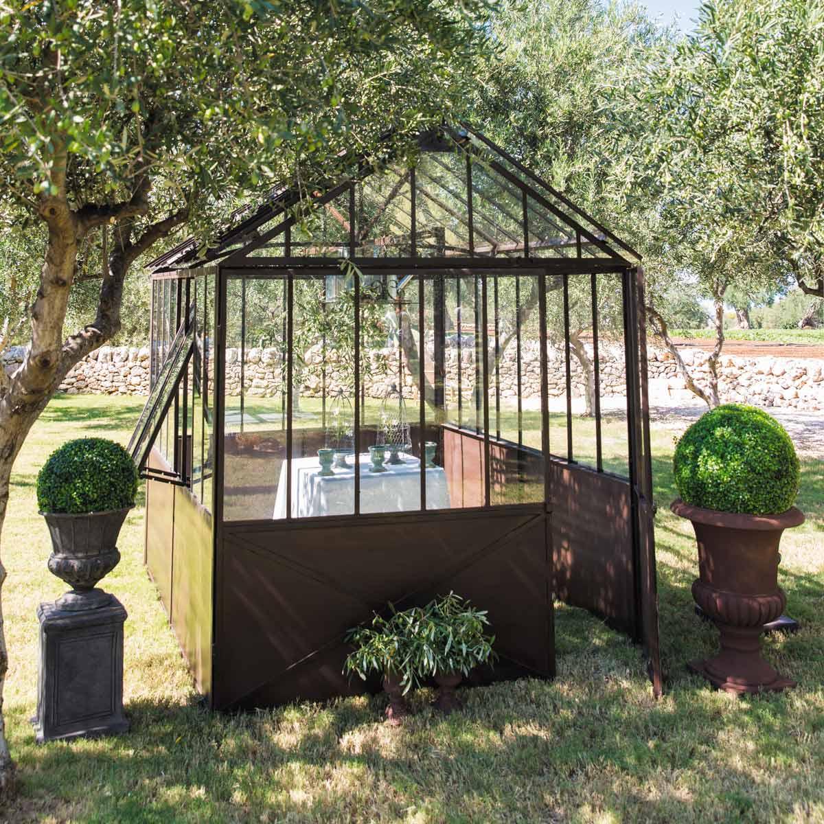 D co avec une serre en m tal dans un jardin for Deco metal jardin