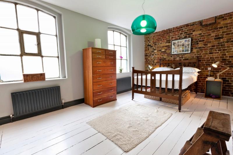 Chambre du loft avec un mur en brique
