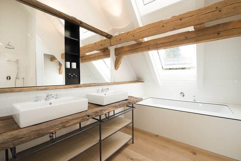 Salle de bains avec poutres en bois dans une ancienne grange