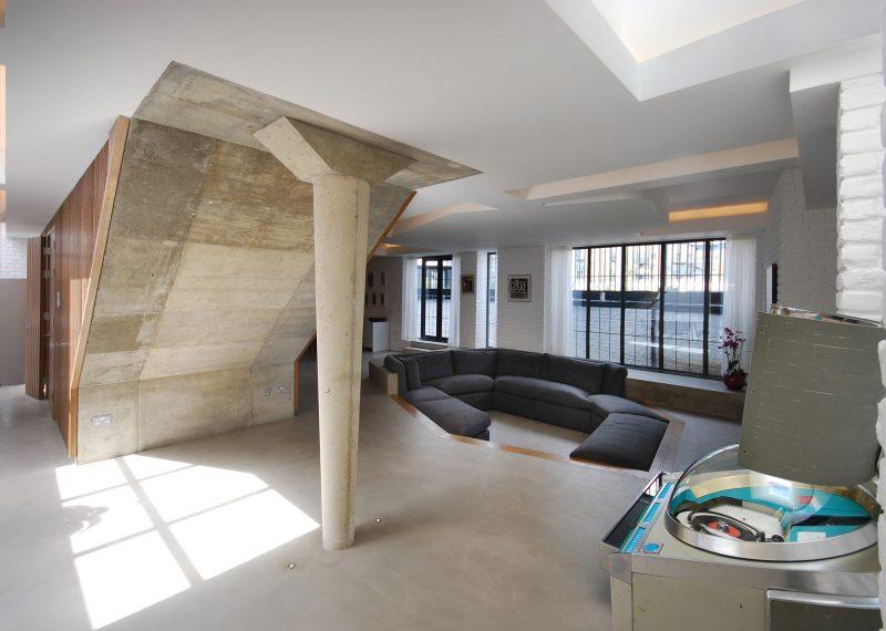 Espace salon en contrebas avec un canapé encastré dans le sol