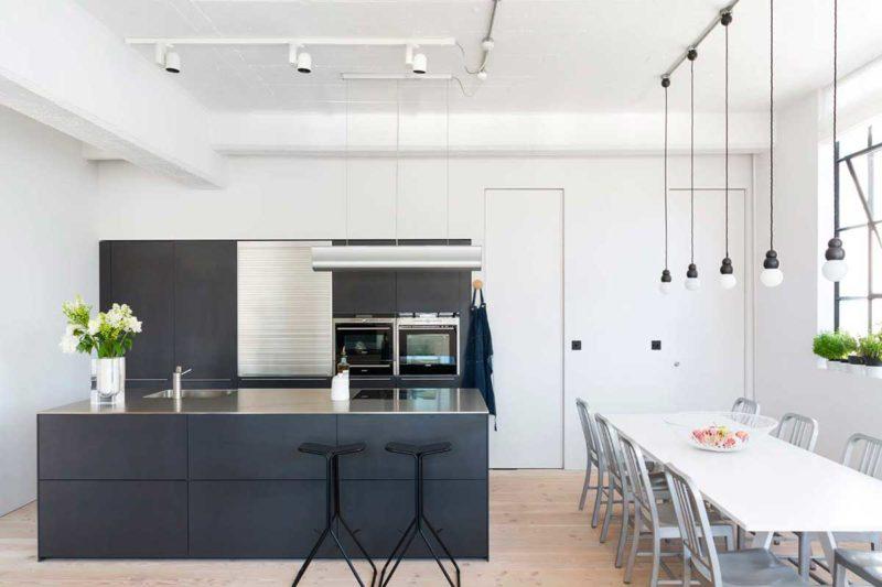 Loft avec cuisine noire et plan de travail inox