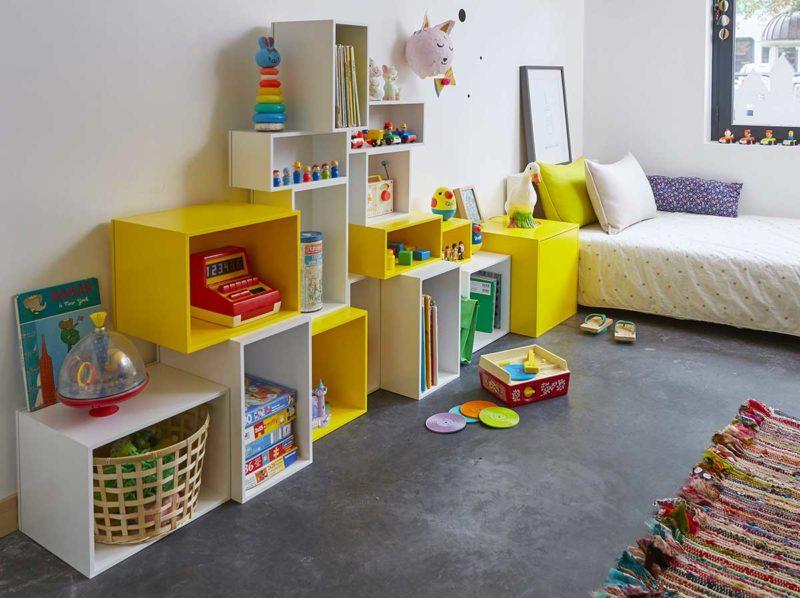 Étagère cube jaune et blanche dans une chambre d'enfant