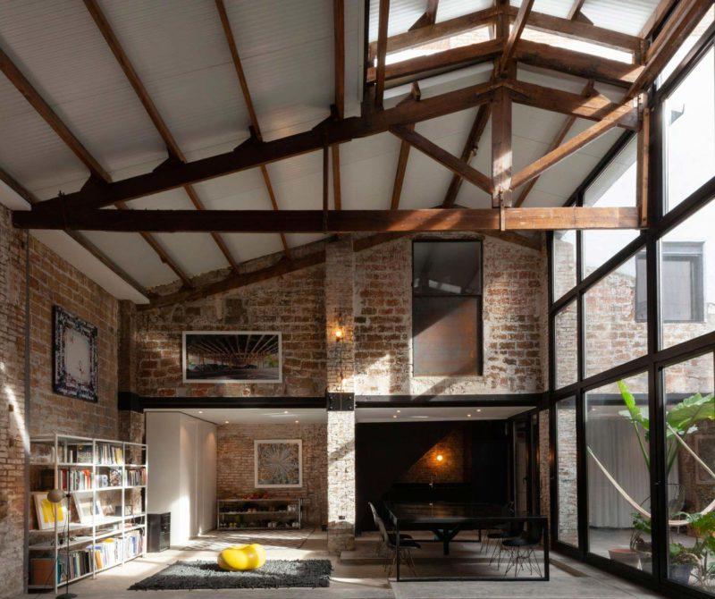 Loft à Barcelone avec charpente en bois apparente et briques