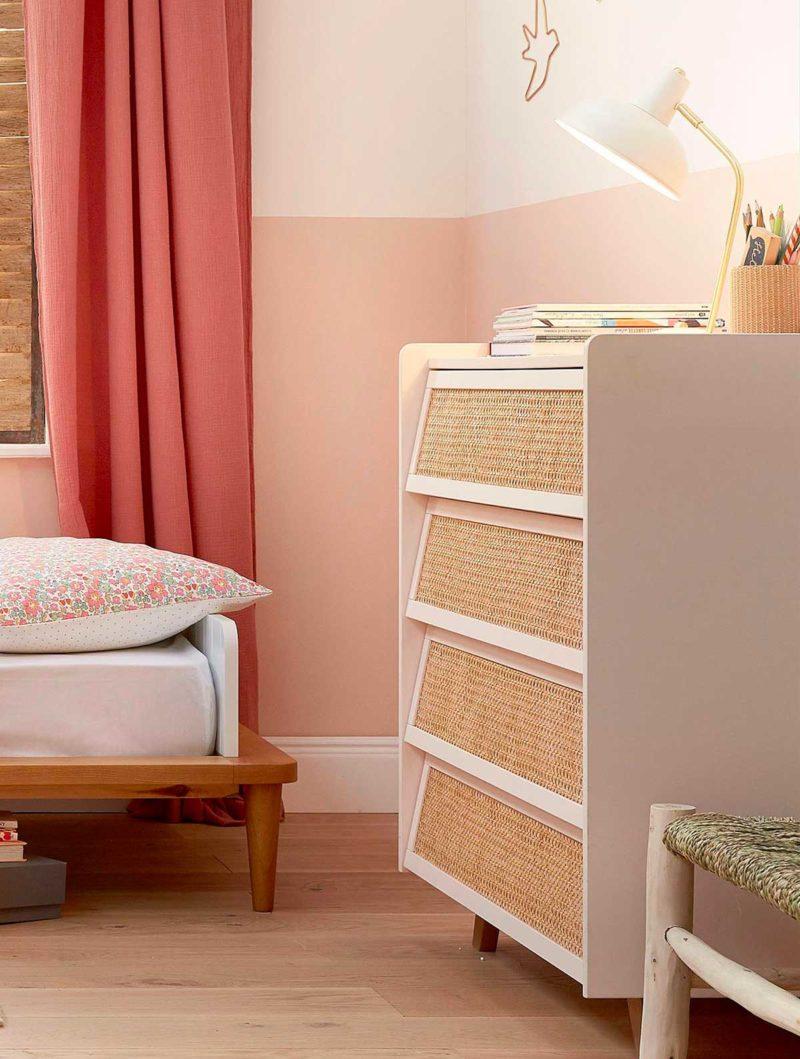 Commode rose pale en cannage dans une chambre d'enfant